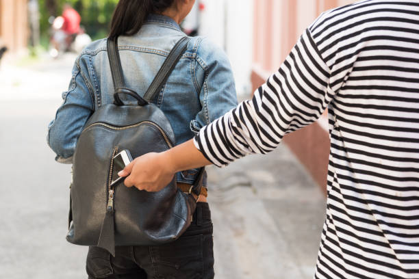 thief stealing smart phone from traveler woman backpack thief stealing smart phone from traveler woman backpack thief stock pictures, royalty-free photos & images