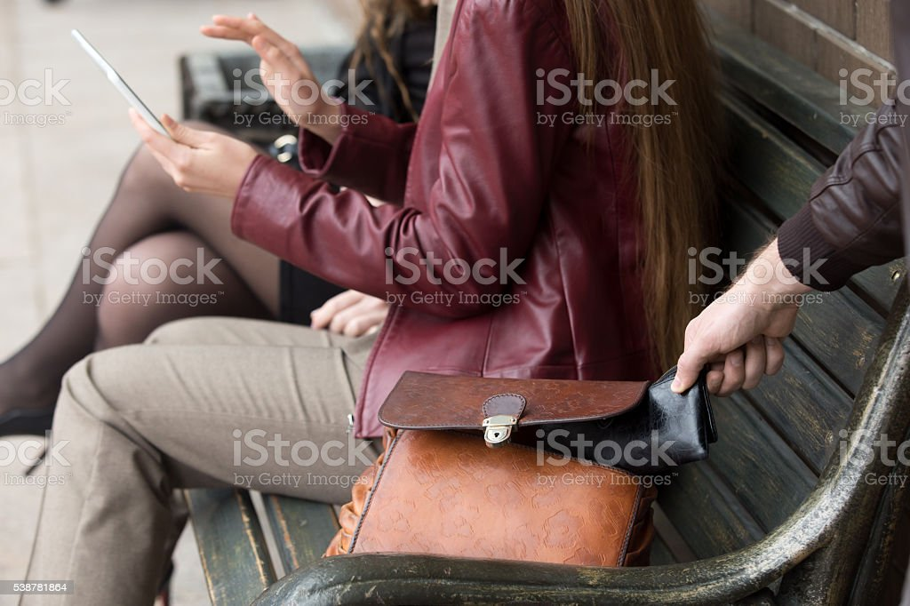 Thief stealing wallet from woman sitting on a bench stock photo