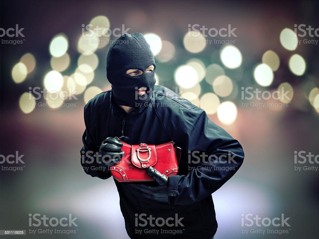 Thief stealing womans handbag stock photo