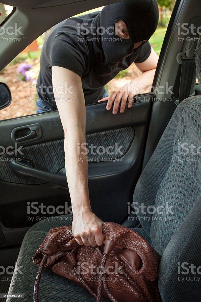 Thief taking bag from car stock photo