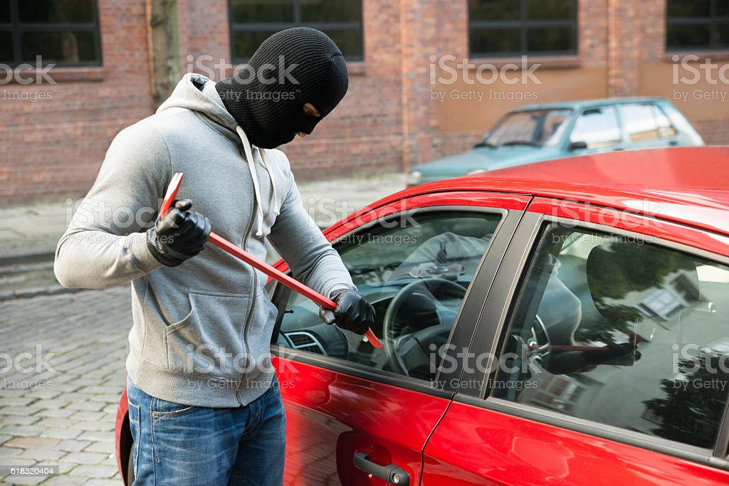 Thief Trying To Smash The Window Of The Car stock photo