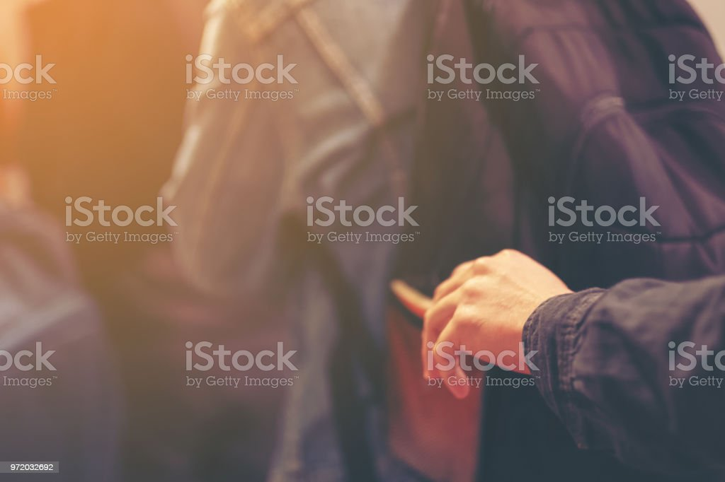Thief trying to steal the wallet in the backpack, Stealing traveling bag on street in big city, crime robber and steal concept stock photo