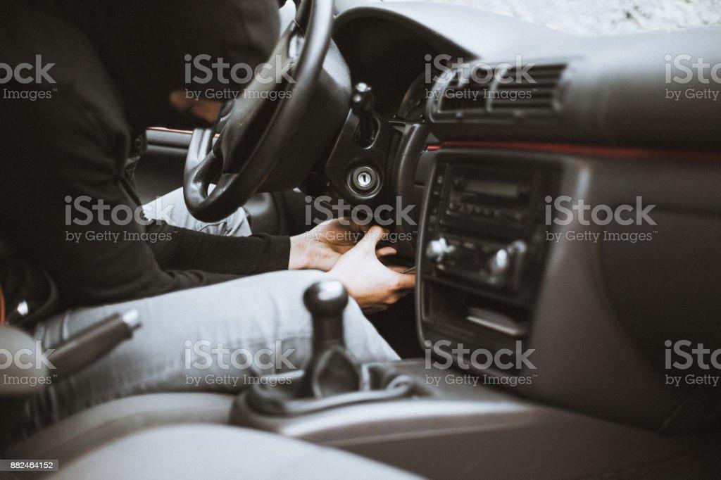Thief trying to unmount plastic case below the steering wheel stock photo