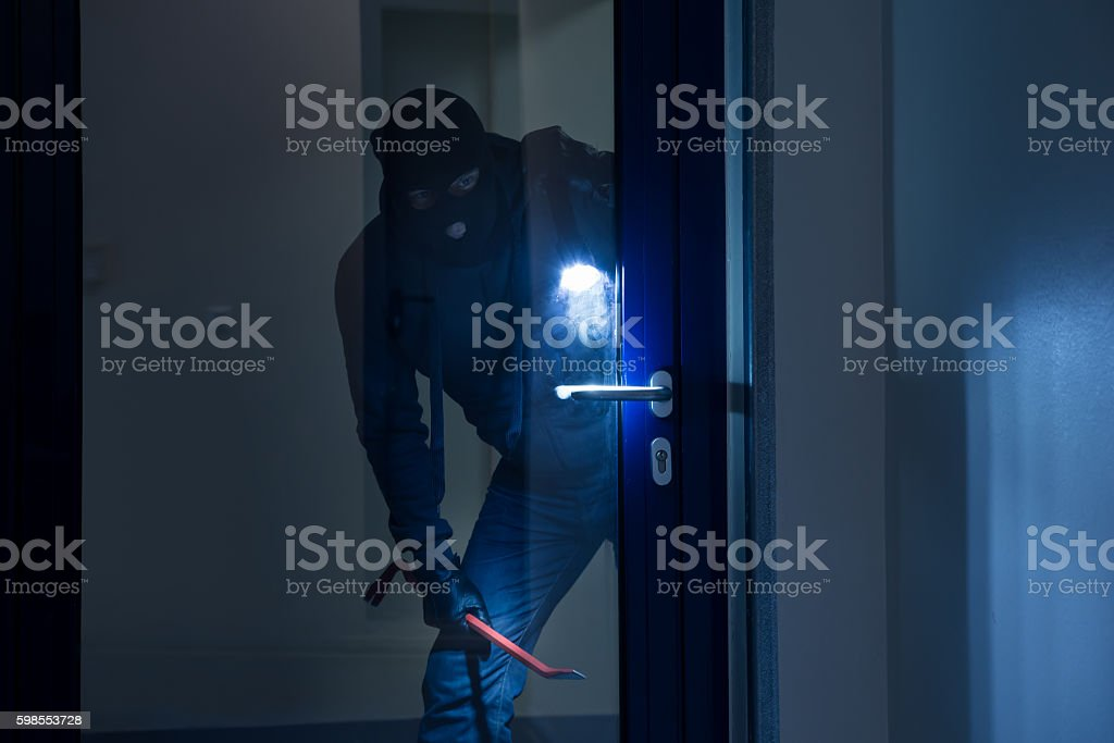 Thief With Flashlight Trying To Break Door stock photo