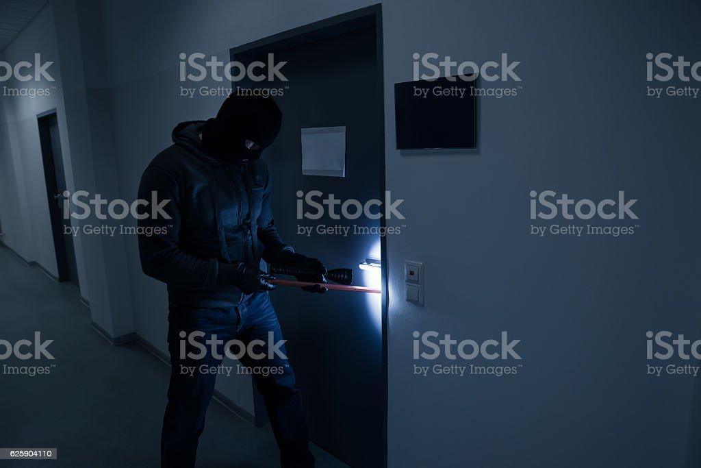 Thief With Flashlight Trying To Break Office Door stock photo