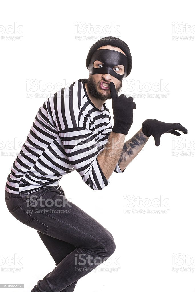 thief with mask quietly slinking stock photo
