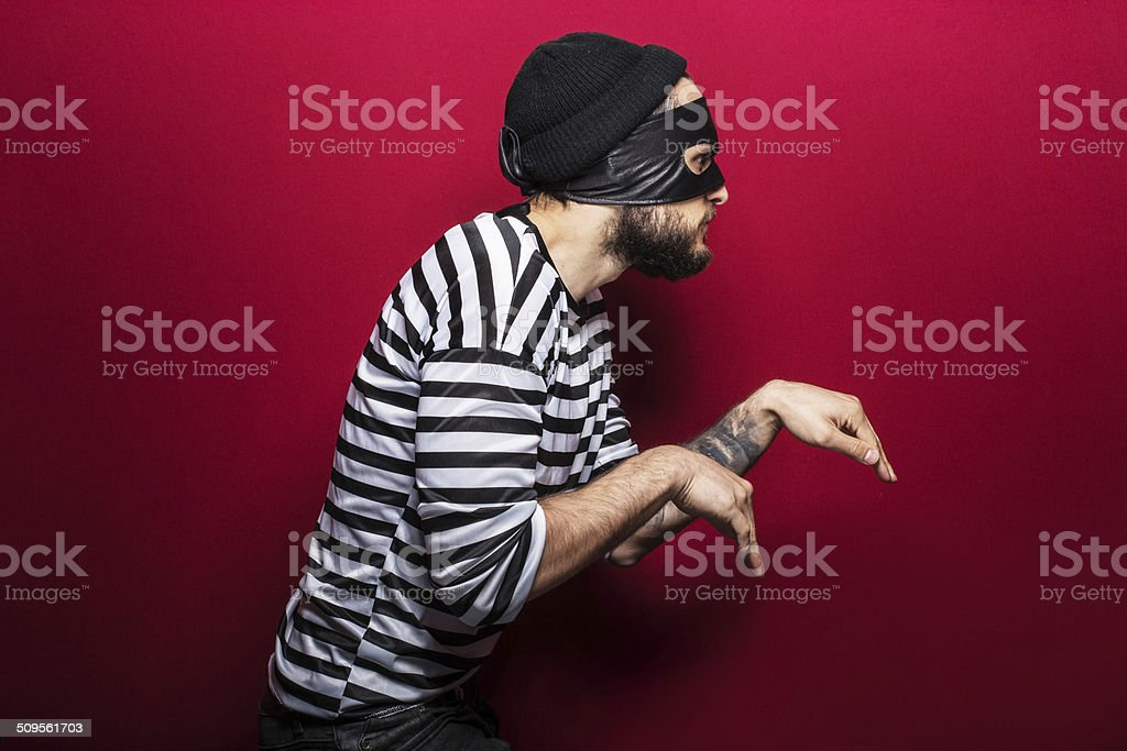 Thief with mask slinking stock photo
