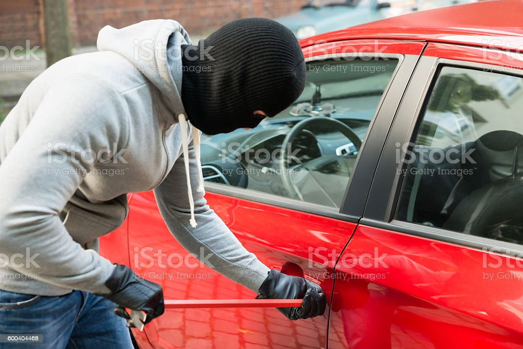 Thief With Mask Using Crowbar To Open Car's Door stock photo