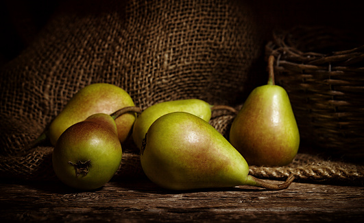 Fresh thigh pears on wooden rustic table with jute background.