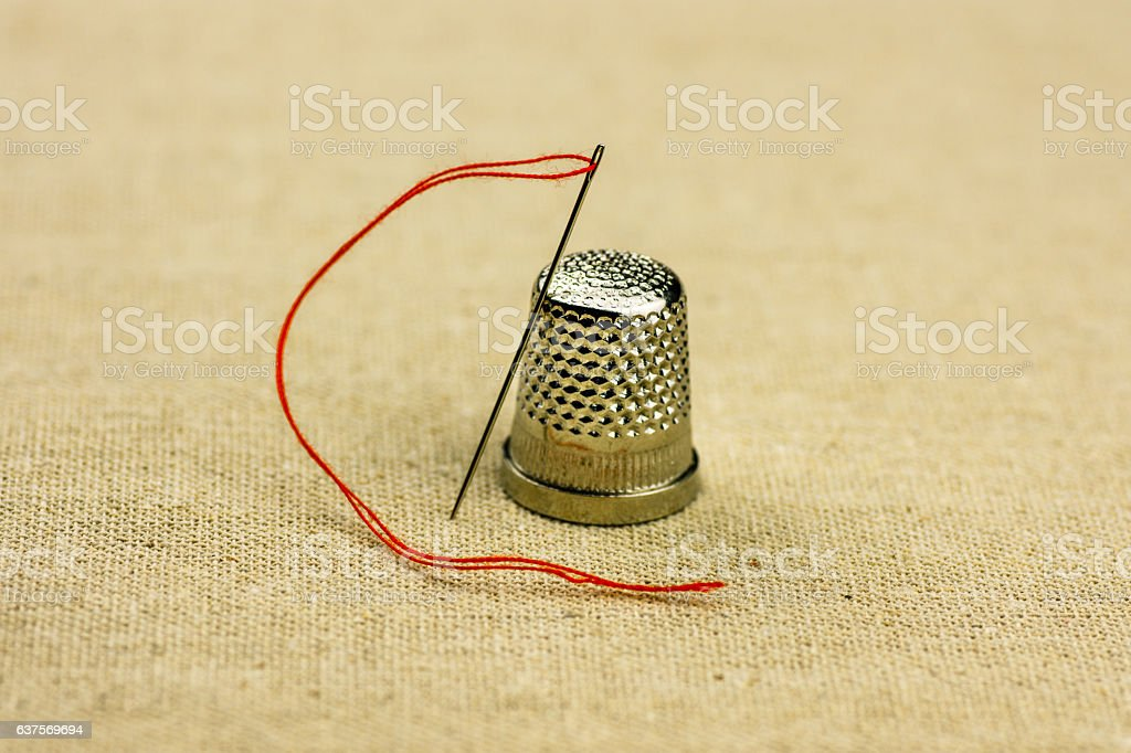 Thimble and sewing needle with a thread on linen cloth stock photo