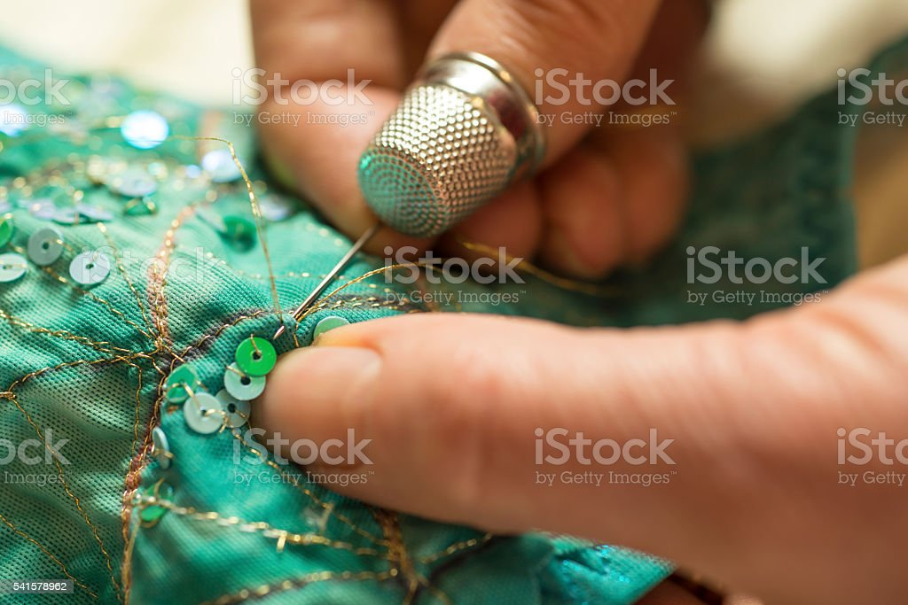 Thimbled Thumb Pushing Needle with Gold Thread Through Garment stock photo