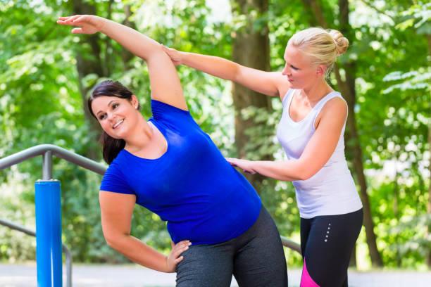 dünn und übergewichtige frau training zusammen - damen sporthose übergröße stock-fotos und bilder