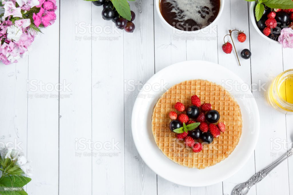 Thin Belgian waffles with honey and berries . Coffee flowers honey on a light background with place for text. stock photo