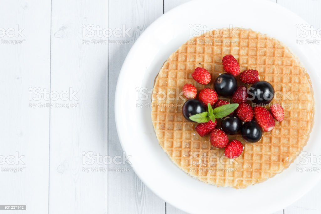 Thin Belgian waffles with honey and berries on a light background with place for text. stock photo