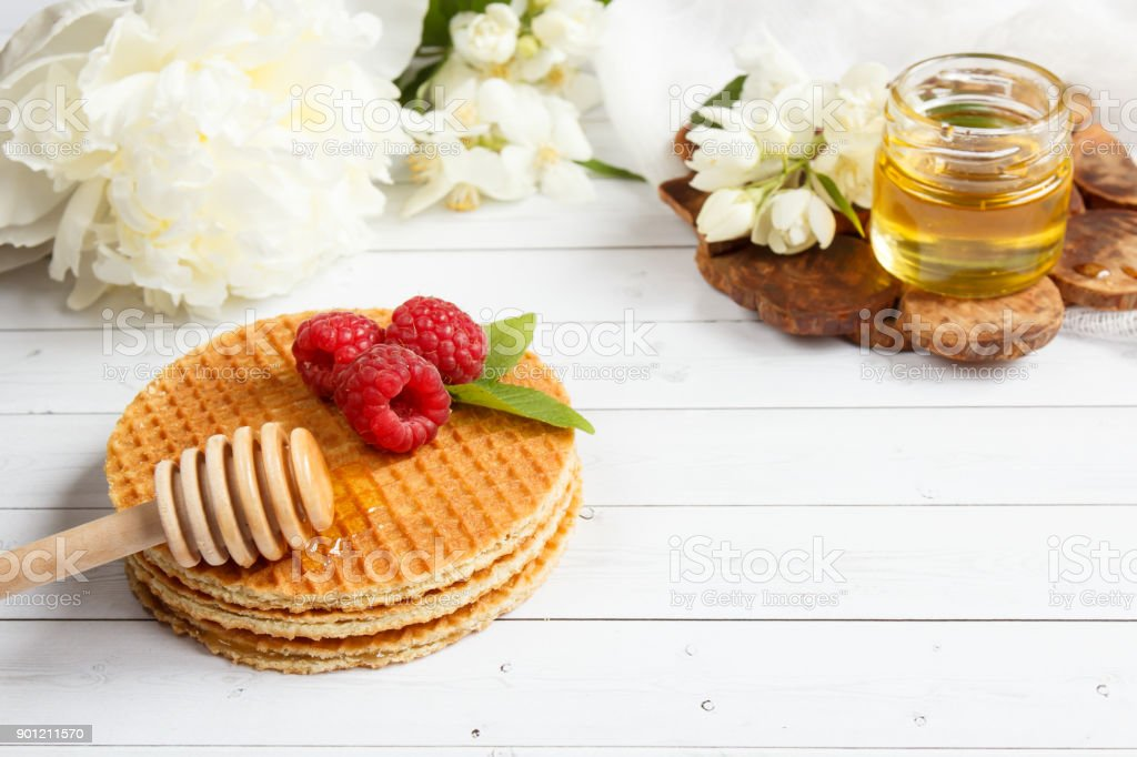 Thin Belgian waffles with honey and raspberries. Jasmine flowers and a jar of honey on a light wooden background stock photo