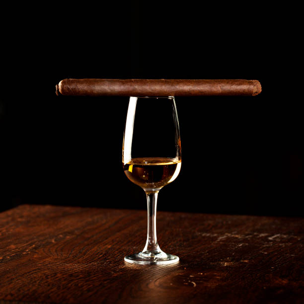 thin cigarillo on black background with glass of cognac - tamara dragovic stock photos and pictures