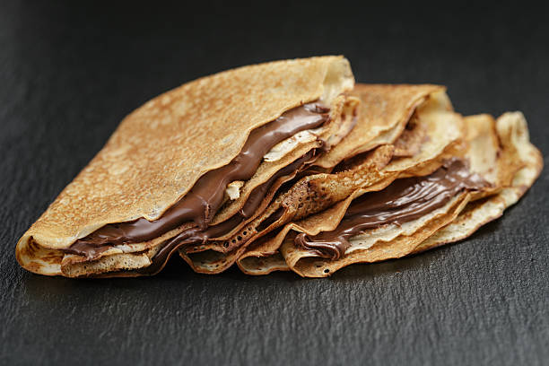 thin crepes or blinis with chocolate cream on slate board - crepe bildbanksfoton och bilder