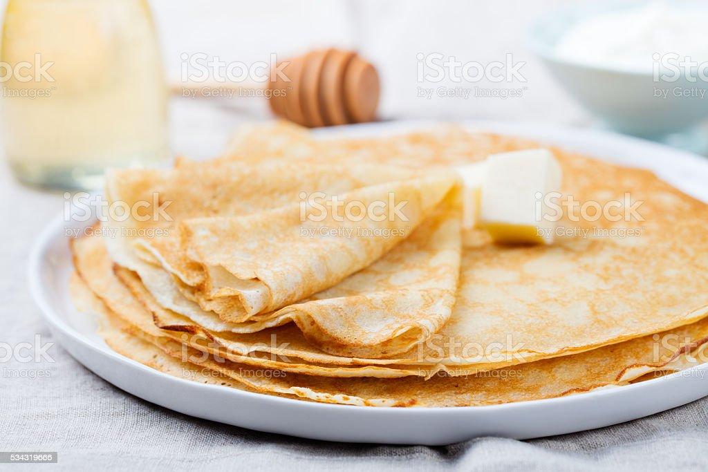Fines crêpes ou des crêpes au beurre, de miel et de la crème aigre - Photo