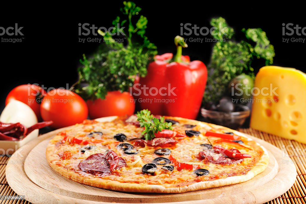 Thin crust pizza with vegetables and cheese in background royalty-free stock photo