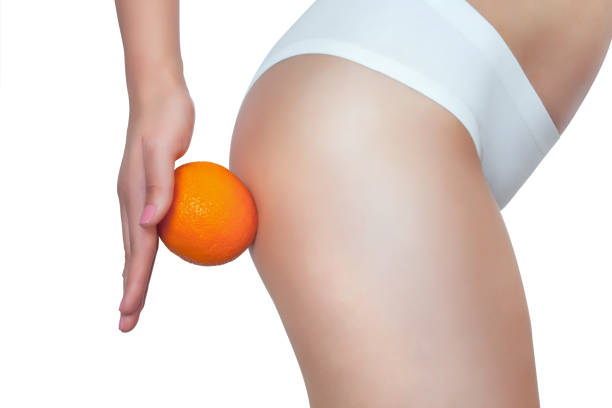 a thin girl is holding an orange by her ass. - deposition stock pictures, royalty-free photos & images