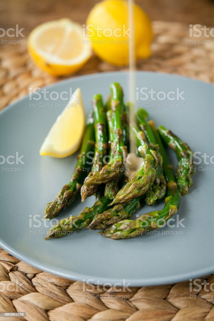 Thin green asparagus in creamy lemon sauce. royalty-free stock photo
