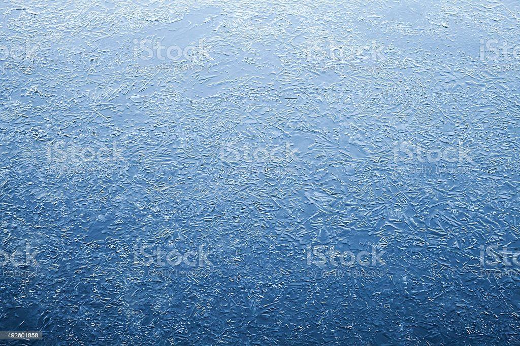 Thin ice layer of frozen river water stock photo
