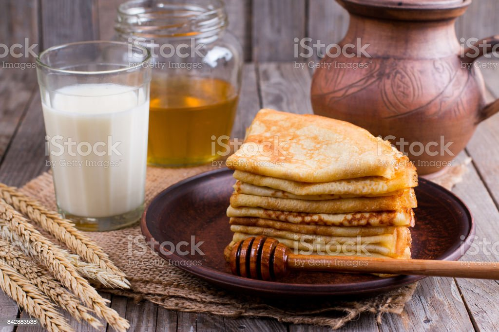 Thin pancakes on a plate with honey and a glass of milk on a wooden background. Tasty breakfast stock photo