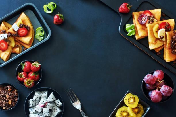 tunna pannkakor med druvor, kiwi, jordgubb, pitaya, honung och choklad granola över mörk bakgrund. utrymme för text. - cactus lime bildbanksfoton och bilder