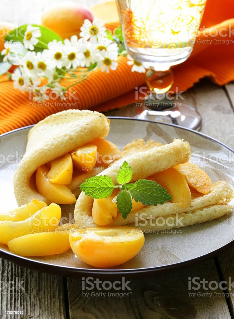 thin pancakes (crepes) with peaches and mint royalty-free stock photo