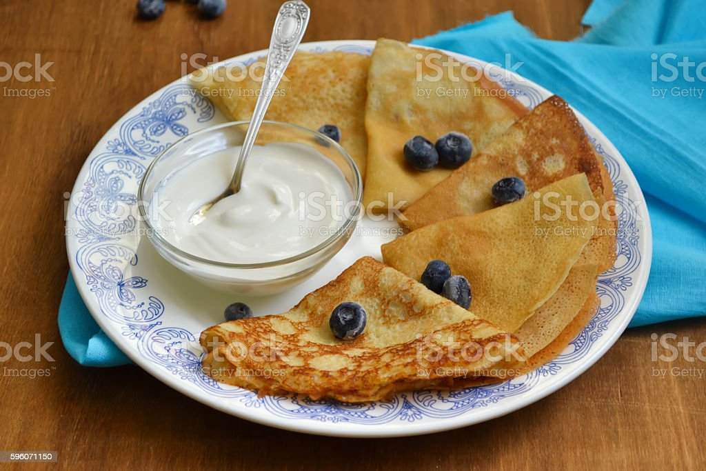 Thin pancakes with sour cream and blueberries, breakfast royalty-free stock photo
