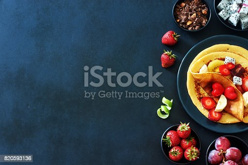 istock Thin pancakes with strawberries, grapes, dragon fruit, golden kiwi and honey over black background with a copy space. 820593136