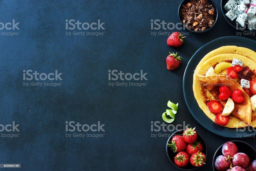 Dünne Pfannkuchen mit Erdbeeren, Trauben, Drachenfrucht, golden Kiwi und Honig über eine textfreiraum auf schwarzem Hintergrund. – Foto