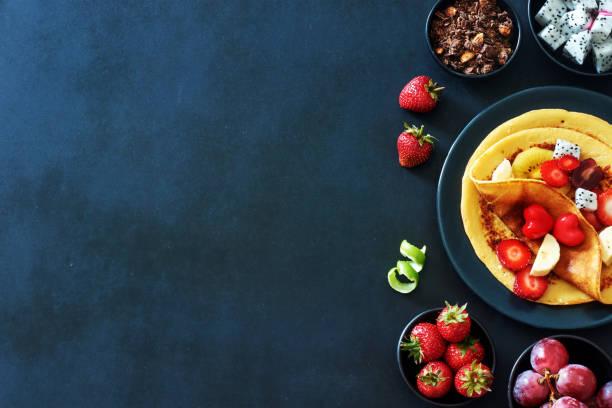 tunna pannkakor med jordgubbar, vindruvor, drakfrukt, gyllene kiwi och honung över svart bakgrund med en kopia-utrymme. - cactus lime bildbanksfoton och bilder
