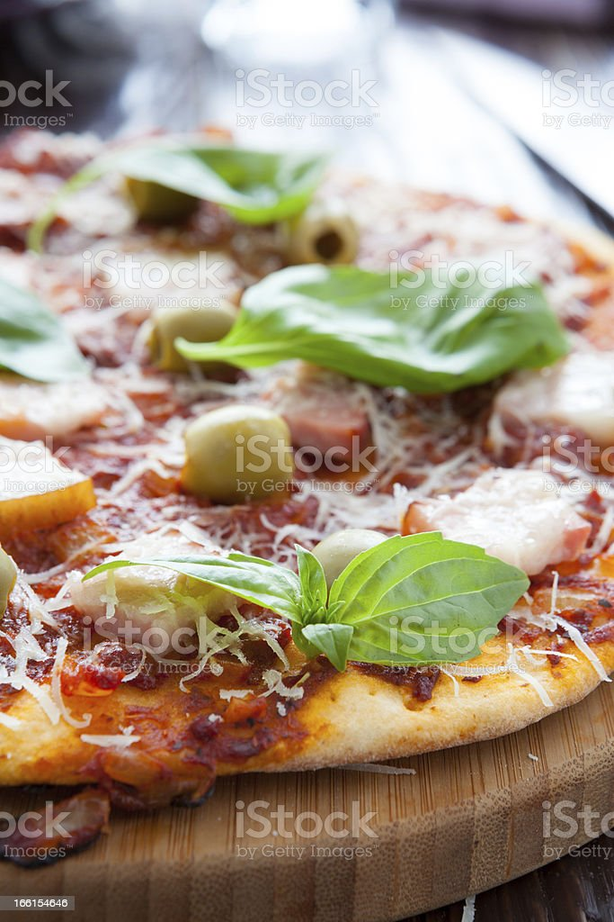 thin pizza with bacon, olives and basil on board royalty-free stock photo