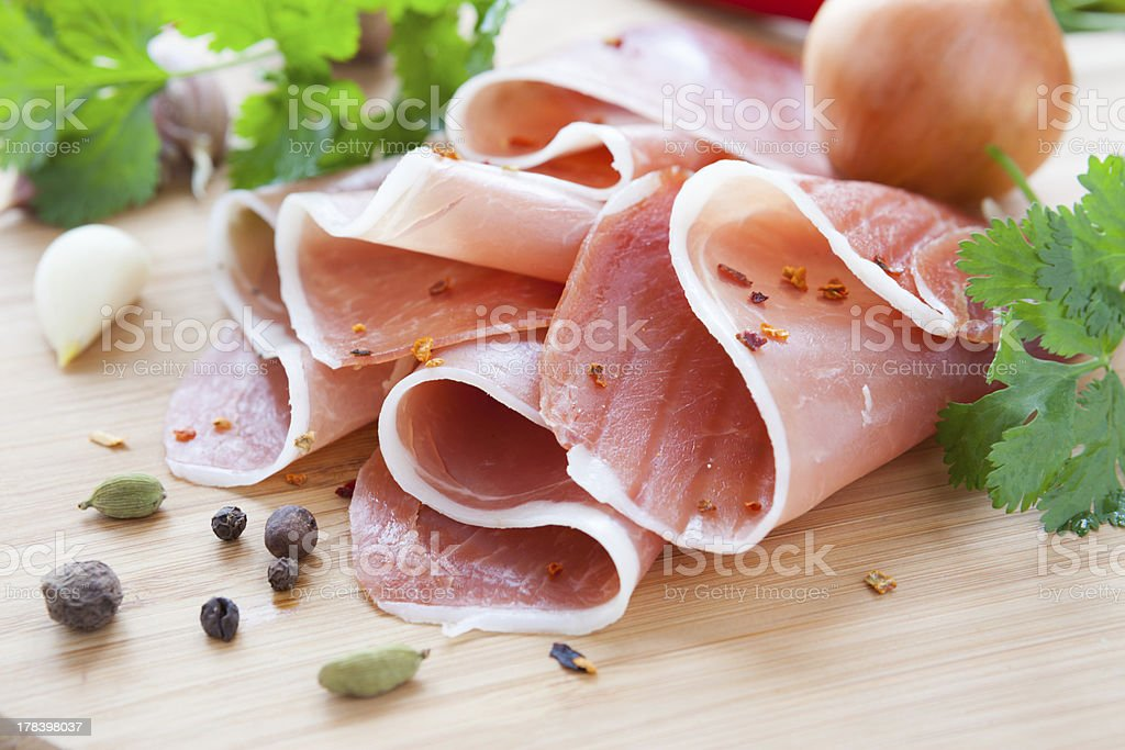 thin slices of ham on a wooden surface royalty-free stock photo