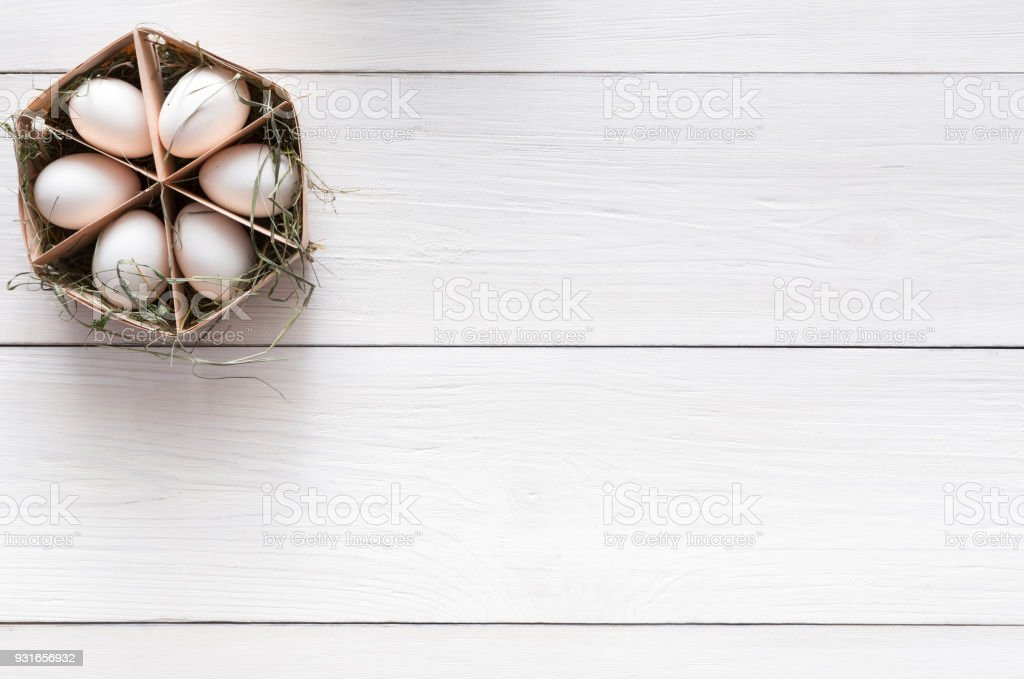 Thin wood box with six eggs on white wooden background, copy space....