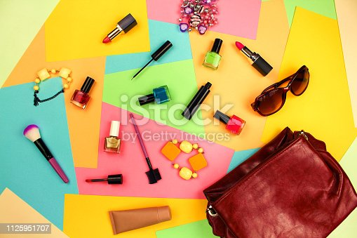 istock Things from open lady purse. Cosmetics and women's accessories fell out of red handbag on colourful background. Top view. Flat lay. 1125951707