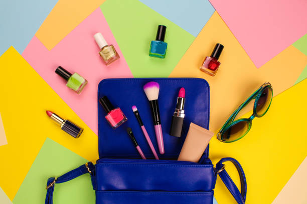 Things from open lady purse. Cosmetics and women's accessories fell out of blue handbag on colourful background. Top view. stock photo