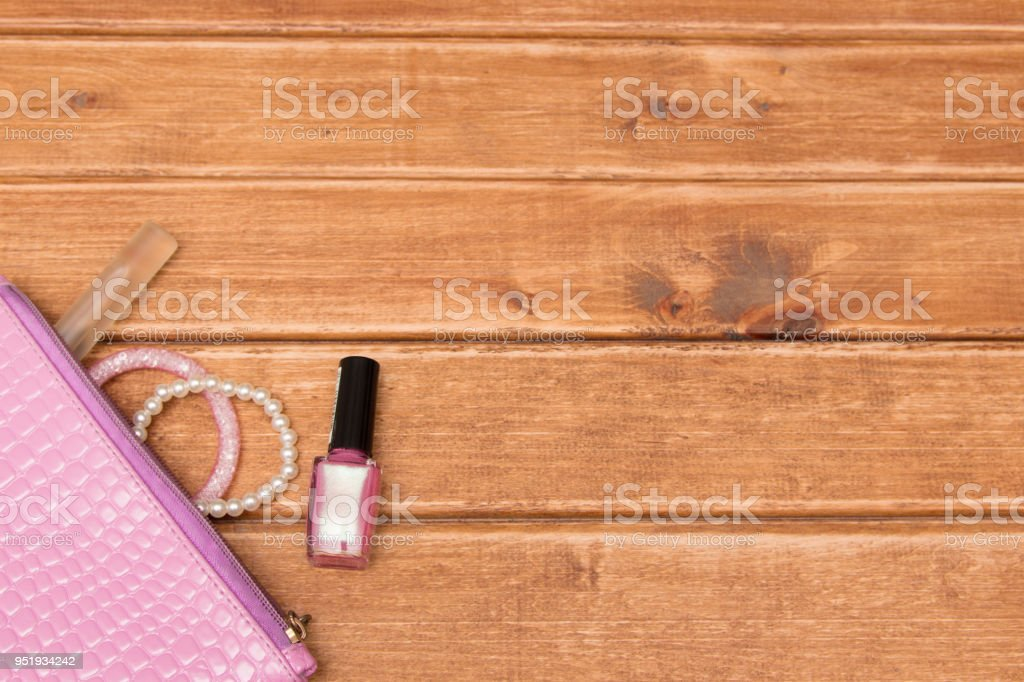Things from open woman purse on wooden background . Cosmetics and...
