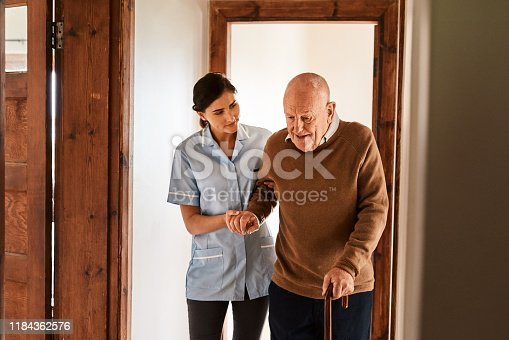 Shot of a young nurse assisting a senior man with a walking stick in a retirement home