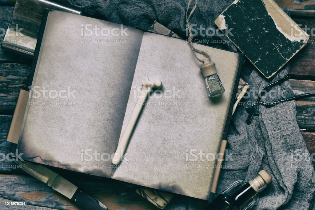 Things hunter for evil, demons, vampires and zombies - an old notebook, a book with spells, a knife, flask of holy water, pen bone, alcohol, a cross. Men's accessories on a dark background. stock photo