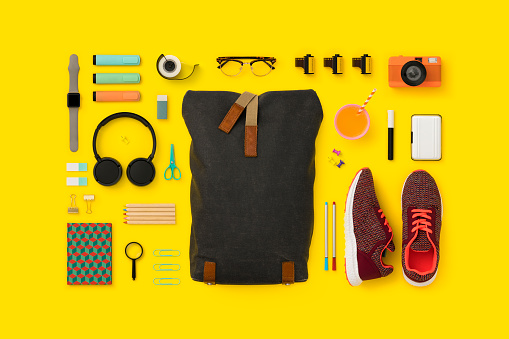 School supplies and backpack flat lay. Back to school flat lay on yellow background