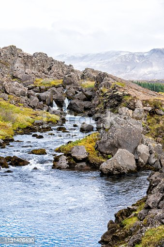 Thingvellir National Park with autumn foliage in Iceland Golden circle and vertical view of small waterfall on rocky trail with blue water landscape