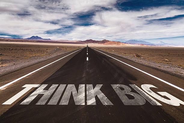 think big schriftliche auf einer wüstenstraße - bedeutungsvolle zitate stock-fotos und bilder