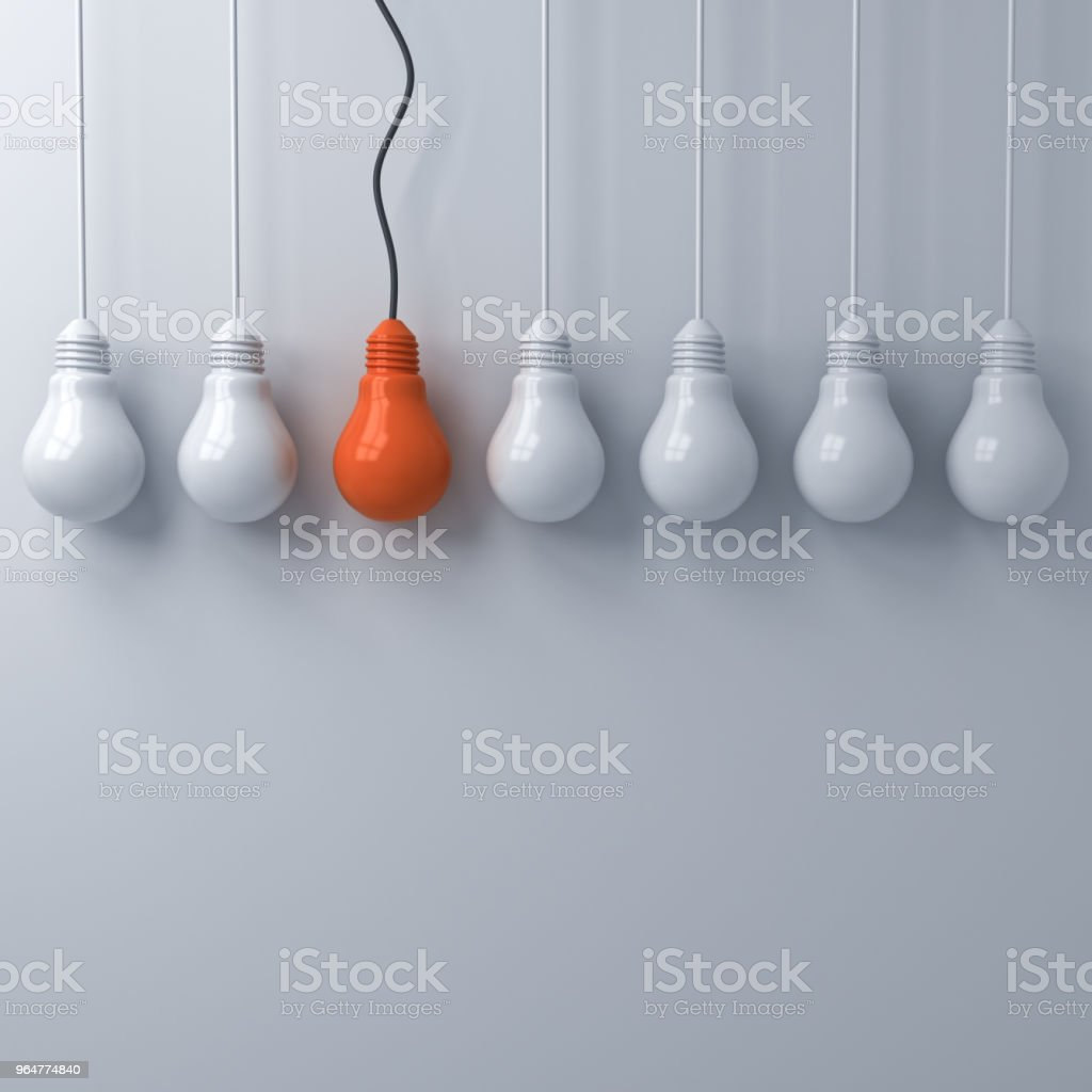 Think different concept , One hanging orange light bulb standing out from the unlit white lightbulbs on white wall background , leadership and individuality creative idea concepts 3D rendering royalty-free stock photo