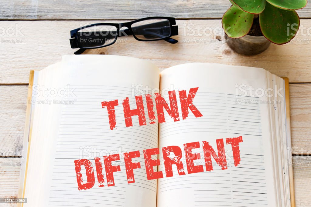 think different on open book, on wooden table stock photo