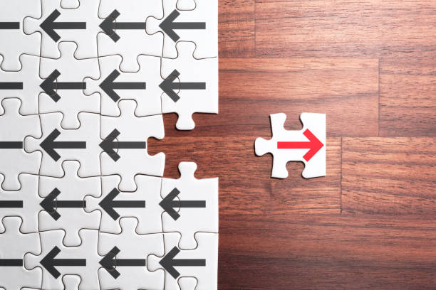 Think different, unique and courage to go alone concept. Jigsaw puzzle piece with red arrow facing the opposite direction from crowd. conflict stock pictures, royalty-free photos & images