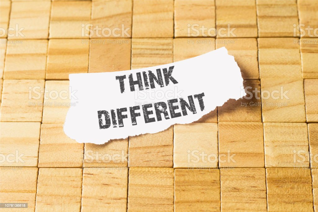 Think different written on piece of paper, on a wood background stock photo