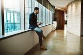 Shot of a young businessman looking thoughtful while using a digital tablet in a modern office