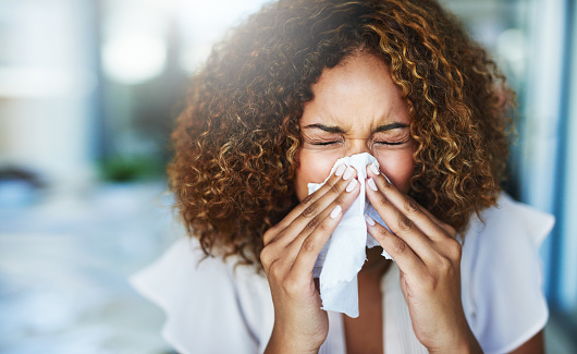 Shot of a frustrated businesswoman using a tissue to sneeze in while being seated in the office